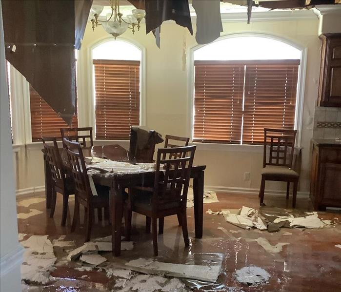 Collapsed ceiling with debris on kitchen table and the floor